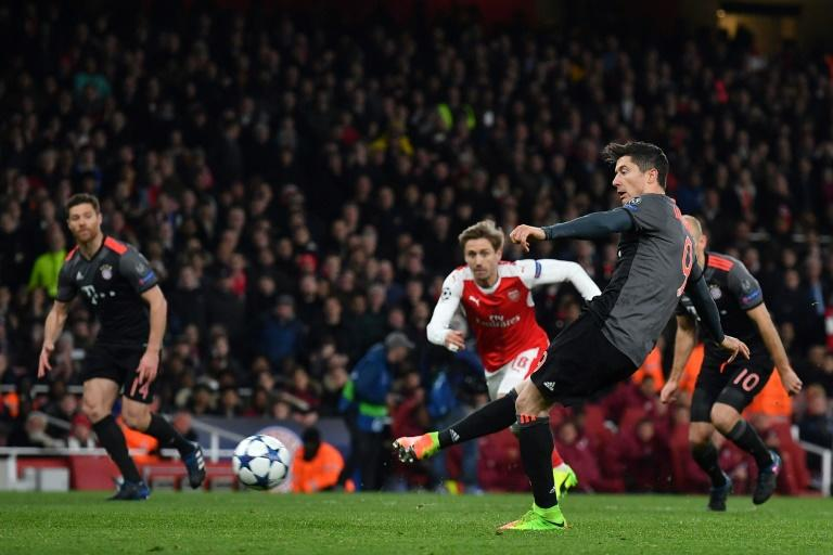 Bayern Munich's forward Robert Lewandowski (R) scores from a penalty during the UEFA Champions League last 16 second leg football match between Arsenal and Bayern Munich at The Emirates Stadium in London on March 7, 2017