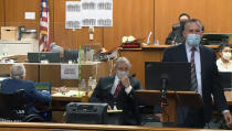 In this still image taken from the Law&Crime Network pool video, real estate heir Robert Durst, left, watches as Deputy District Attorney John Lewin, right, presents a new round of opening statements in the murder case against Durst after a 14-month recess due to the coronavirus pandemic as Durst's defense lawyer Dick DeGuerin, center, looks on in Los Angeles County Superior Court in Inglewood, Calif., Tuesday, May 18, 2021. (Law&Crime Network via AP, Pool)