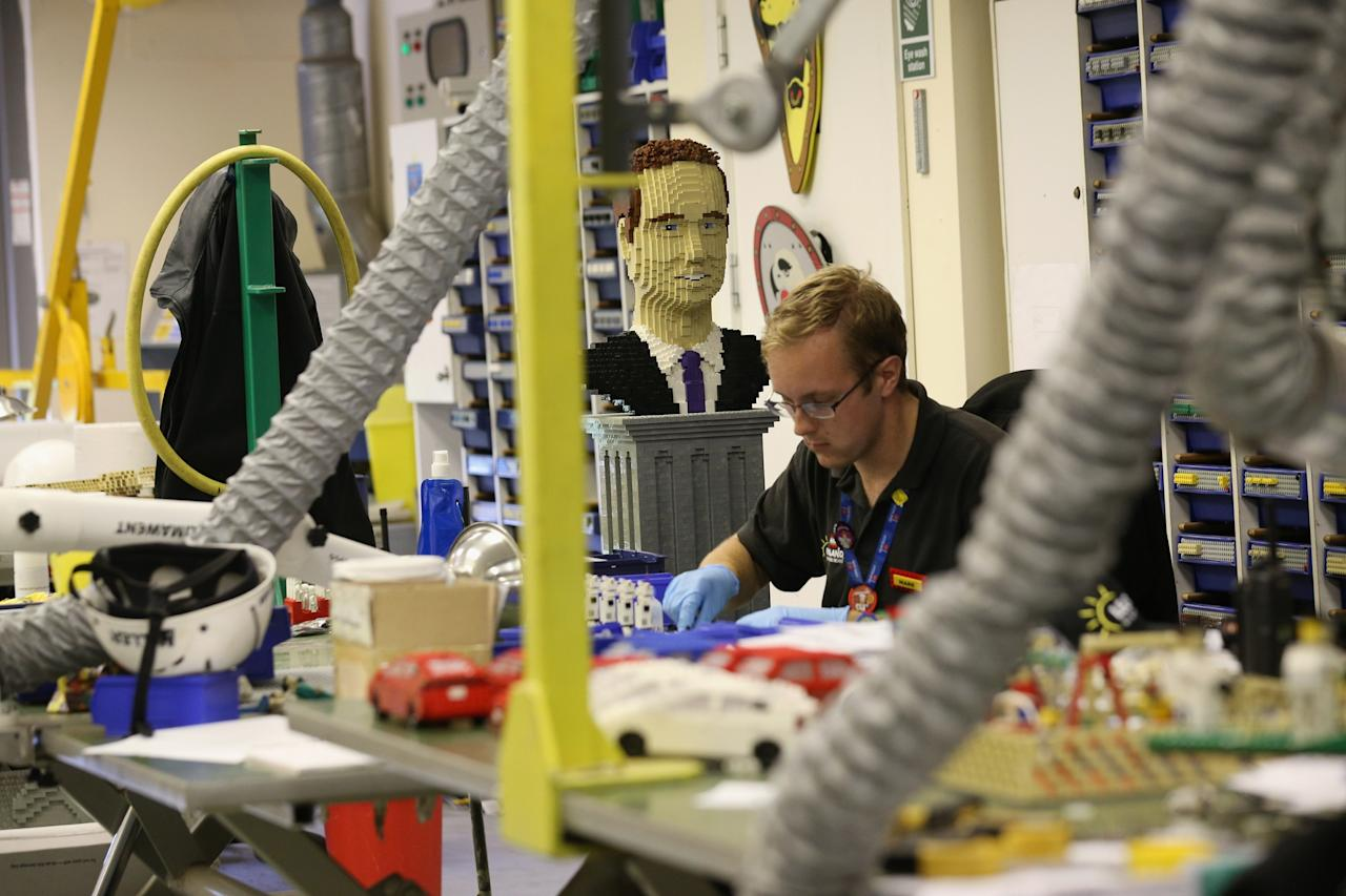 WINDSOR, ENGLAND - JULY 03: A LEGO head of Prince William next to Mark Boyce, a Model Maintenance Assistant, as he creates Start Wars LEGO models in the Model Making Studio at the LEGOLAND Windsor Resort on July 3, 2013 in Windsor, England. LEGOLAND Windsor Resort, which has been open since 1996, has 55 interactive rides and attractions and thousands of LEGO models made from around 80 million individual bricks. LEGOLAND Windsor employs 4 Model Makers who design, build and maintain all of the LEGO models on site. (Photo by Oli Scarff/Getty Images)