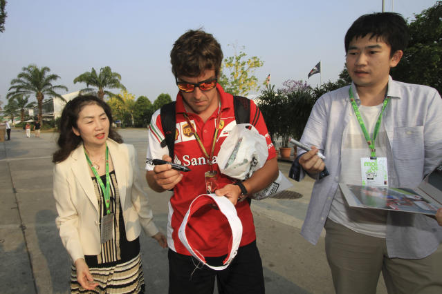 Ferrari driver Fernando Alonso, center, of Spain signs autographs for his fans as he arrives at the paddock for a practice session ahead of the Malaysian Formula One Grand Prix at Sepang International Circuit in Sepang, Malaysia, Friday, March 28, 2014. (AP Photo/Peter Lim)