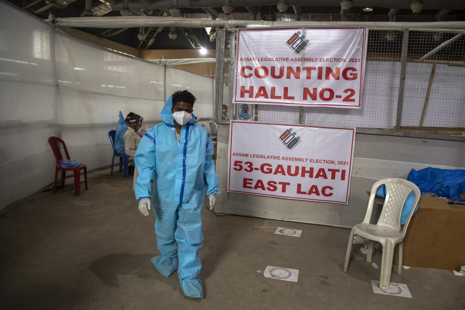 A counting agent in protective suit walks past officials during the counting of votes of Assam state assembly election in Gauhati, India, Sunday, May 2, 2021. With Indian hospitals struggling to secure a steady supply of oxygen, and more COVID-19 patients dying amid the shortages, a court in New Delhi said it would start punishing government officials for failing to deliver the life-saving items. (AP Photo/Anupam Nath)