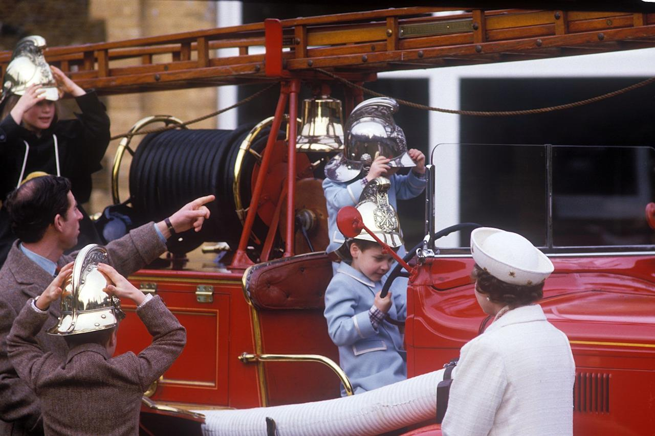 """Queen Elizabeth watches as Prince Harry (pictured putting on his helmet) and Prince William play on a vintage fire engine — <a href=""""https://people.com/royals/baby-prince-william-makes-his-first-appearance-on-the-crown-see-the-photos/"""">in matching coats</a>! — in 1988."""