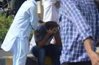 KARACHI, PAKISTAN, MAY 22: A weeping Pakistani man is being comfort at the site of a passenger plane crash in Karachi, Pakistan, May 22, 2020. A Pakistani passenger plane with at least 100 people on board crashed in a residential area in the Pakistani city of Karachi on Friday, the country's civil aviation agency said. (Photo by H.KHAN/Anadolu Agency via Getty Images)