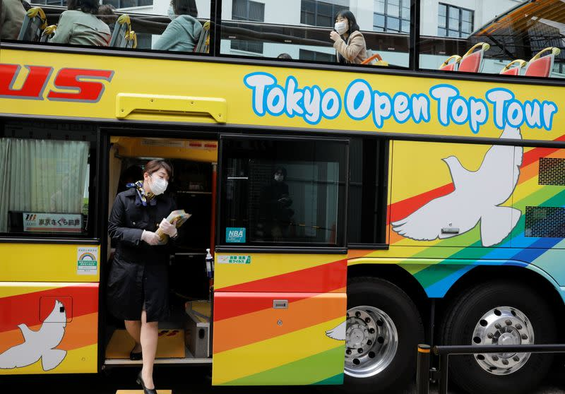 A tour guide of Hato Bus Co. works at an open-top sightseeing bus as the tour service resumed after Japan's government lifted the coronavirus disease (COVID-19) state of emergency in the Tokyo area, in Tokyo