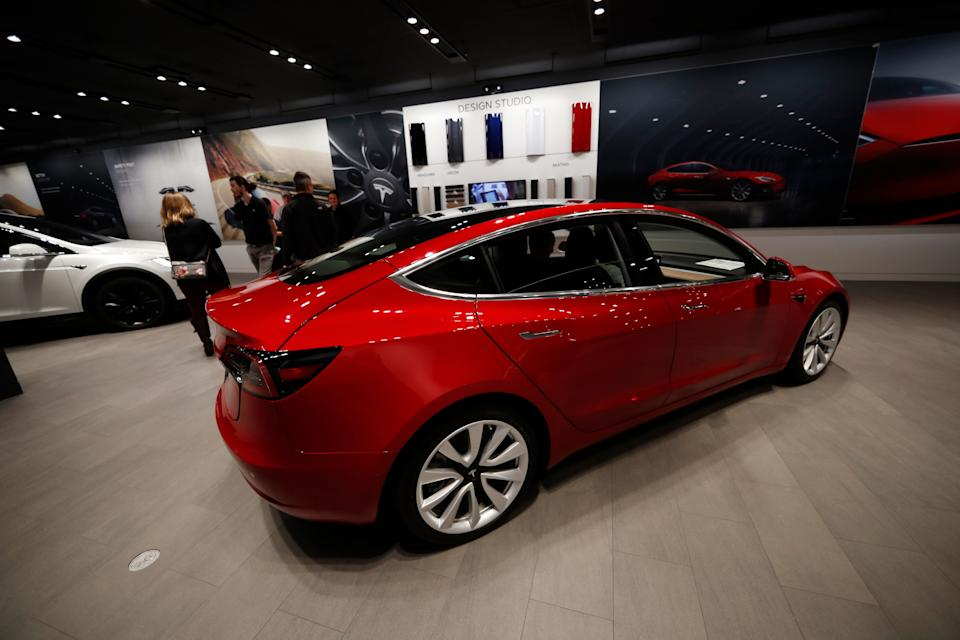 FILE--In this Saturday, Feb. 9, 2019, file photograph, buyers look over a Model 3 in a Tesla store in Cherry Creek Mall in Denver. (AP Photo/David Zalubowski, File)