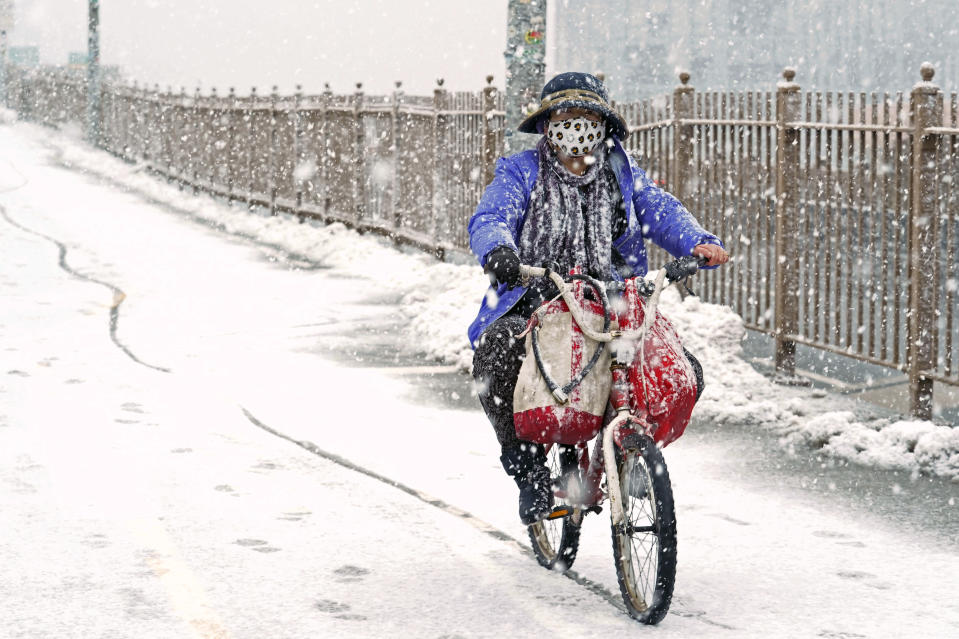 A woman rides a bicycle across the Brooklyn Bridge during a snowstorm, Sunday, Feb. 7, 2021, in the Brooklyn borough of New York. It was the second time in less than a week the area has been buffeted by heavy snowfall. (AP Photo/Kathy Willens)