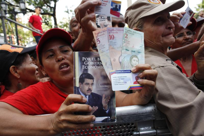 FILE - In this Aug. 21, 2018 file photo, pro-government supporters cheer as some hold up new banknotes and patriot identification cards during a rally in Caracas, Venezuela. Little noticed abroad amid the turmoil unleashed by the opposition's renewed push to oust President Nicolas Maduro in early 2019, Venezuela's central bank devalued the country's bolivar currency on Jan. 28, 2019 by 50 percent, eclipsing the parallel black market rate. (AP Photo/Ariana Cubillos, File)