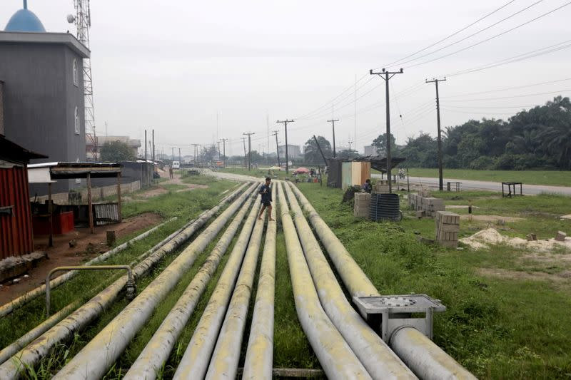 FILE PHOTO: A woman walks over pipelines crisscrossing Ogoniland in Rivers State