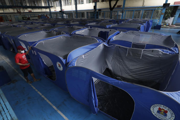 A man walks past tents set-up at a school converted into an evacuation center as they prepare for Typhoon Vamco in Manila, Philippines on Wednesday, Nov. 11, 2020. Typhoon Vamco blew closer Wednesday to a northeastern Philippine region still struggling to recover from a powerful storm that left a trail of death and destruction just over a week ago, officials said, adding that thousands of villagers were being evacuated again to safety. (AP Photo/Aaron Favila)