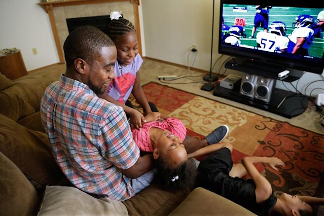 Adrian Arrington, a former safety at Eastern Illinois University, plays with his children from left, Andria Arrington, Ayana Lucero, and Isaiah Dye, while talking about enduring five concussions while playing, some so severe he has says he couldn't recognize his parents afterward, during an interview with The Associated Press at his home Tuesday, July 29, 2014, in Bloomington Ill. Subsequent headaches, memory loss, seizures and depression made it difficult to work or even care for his children. The NCAA agreed to settle a class-action head-injury lawsuit by creating a $70 million fund to diagnose thousands of current and former college athletes to determine if they suffered brain trauma playing football, hockey, soccer and other contact sports. Arrington was the lead plaintiff in the lawsuit. (AP Photo/Seth Perlman)