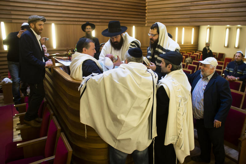 FILE - In this Oct. 29, 2012 file picture mohel doctor Yacov Gassinovitch, center, is surround by other Rabbis and relatives as he holds eight days old Jonathan during the boy's circumcision at synagogue in Berlin. German Parliament is  expected to vote on legislation clarifying the legality of infant male circumcision for religious reasons. The government drew up the legislation after a court in June ruled the practice could amount to criminal bodily harm — prompting outrage in Germany's Jewish and Muslim communities. (AP Photo/Markus Schreiber)