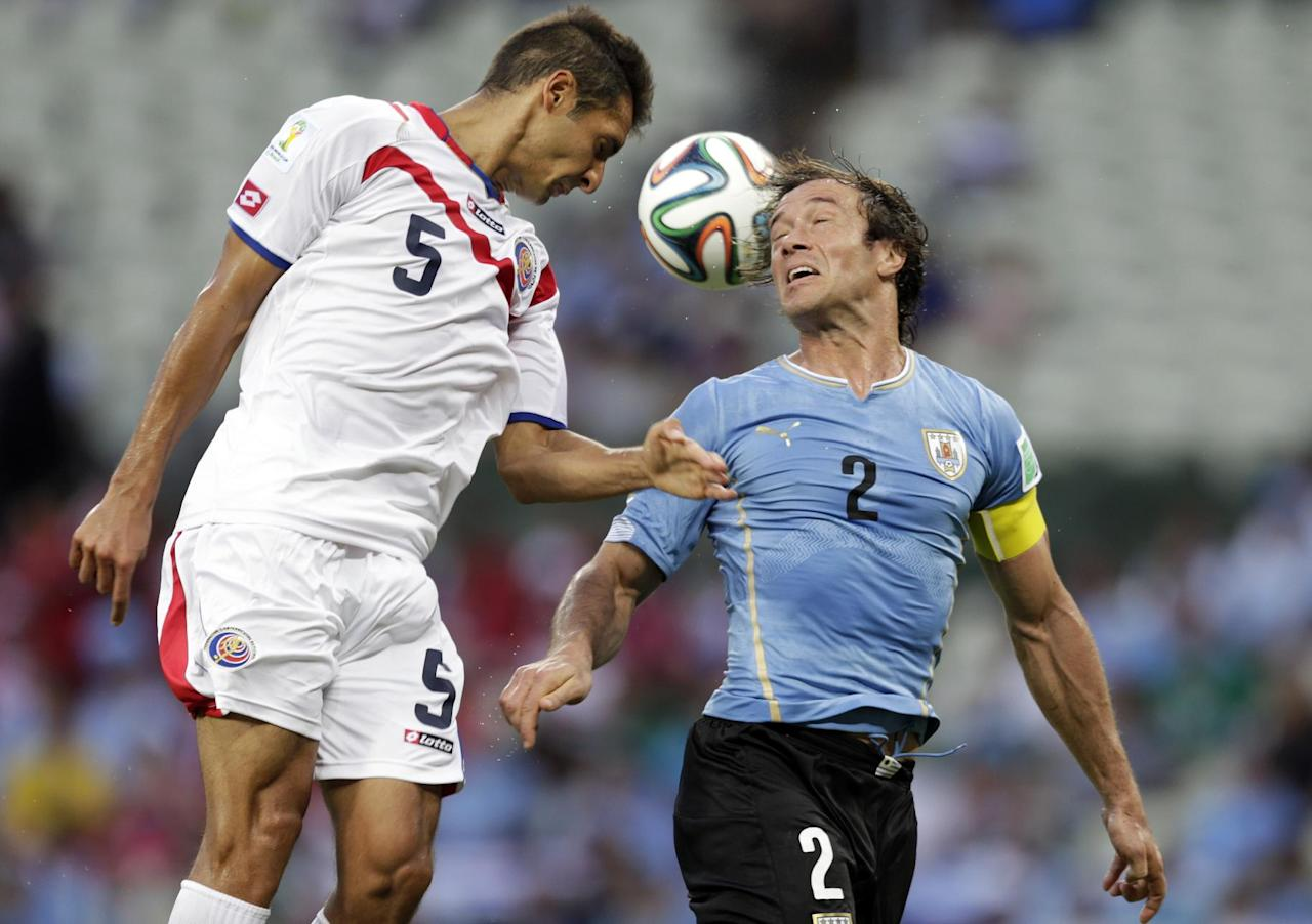 Costa Rica's Celso Borges (5) heads the ball past Uruguay's Diego Lugano (2) during the group D World Cup soccer match between Uruguay and Costa Rica at the Arena Castelao in Fortaleza, Brazil, Saturday, June 14, 2014.  (AP Photo/Fernando Llano)