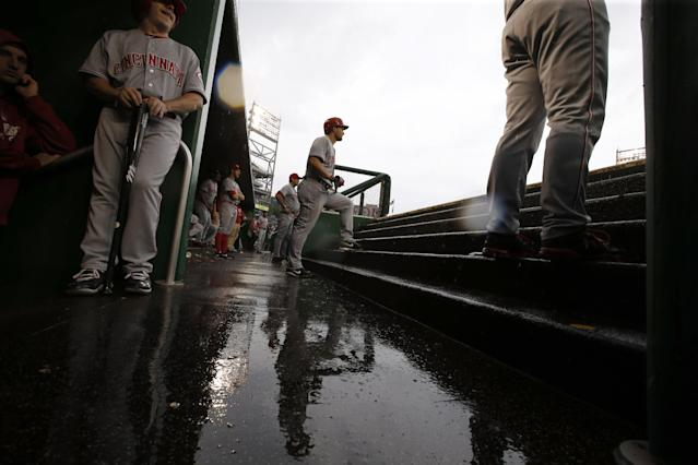 Cincinnati Reds' Chris Heisey, center, stands on the steps as he prepares to bat in the rain during the sixth inning of a baseball game against the Washington Nationals at Nationals Park on Wednesday, May 21, 2014, in Washington. (AP Photo/Alex Brandon)