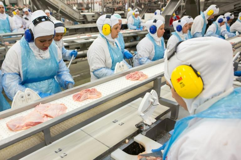 People work at a production line of the JBS-Friboi chicken processing plant during an inspection visit from Brazilian Agriculture Minister Blairo Maggi and technicians of the ministry in Lapa, Parana State, Brazil on March 21, 2017