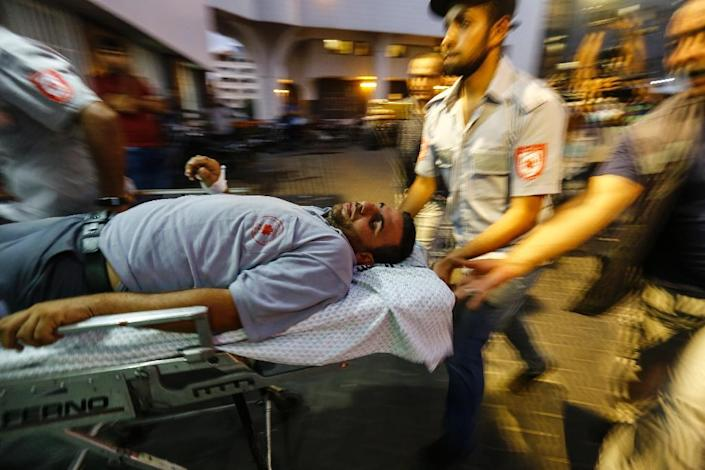 Palestinian paramedics wheel an injured man into the al-Shifa hospital in Gaza City after he was injured by Israeli forces during protests along the border east of Gaza City on July 20, 2018 (AFP Photo/ANAS BABA)