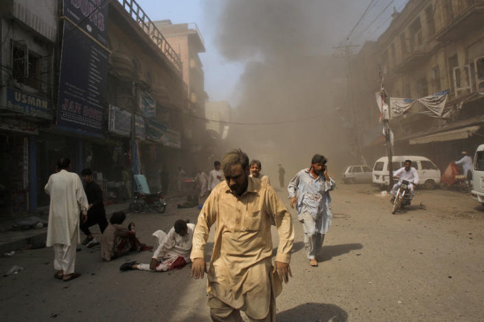Pakistani men rush away from the site of a blast shortly after a car explosion in Peshawar, Pakistan, Sunday, Sept. 29, 2013. A car bomb exploded on a crowded street in northwestern Pakistan Sunday, killing scores of people in the third blast to hit the troubled city of Peshawar in a week, officials said. (AP Photo/Mohammad Sajjad)