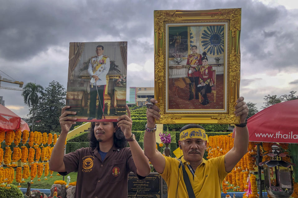 Supporters of monarchy display images of Thailand's King Maha Vajiralongkorn and Queen Suthida during a gathering to show their support at Ramkhamhaeng University in Bangkok, Thailand, Wednesday, Oct. 21, 2020. A small group of royalist gathered to show their loyalty to the monarchy and declare they will defend the institution from any attacks. Royalists this week stepped up their activities online and in the streets, in counterpoint to ongoing student-led protests whose demands include reform of the monarchy to have it to better conform with democratic norms. (AP Photo/ Peerayot Lakkananukul)