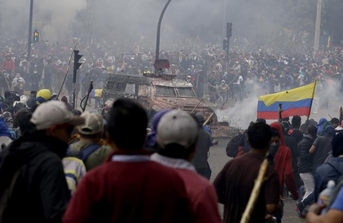 An armored vehicle drives towards a crowd of anti-government demonstrators protesting against President Lenin Moreno and his economic policies, in Quito, Ecuador, Tuesday, Oct. 8, 2019. The protests, which began when President Lenin Moreno's decision to cut subsidies led to a sharp increase in fuel prices, have persisted for days and clashes led the president to move his besieged administration out of Quito. (AP Photo/Fernando Vergara)