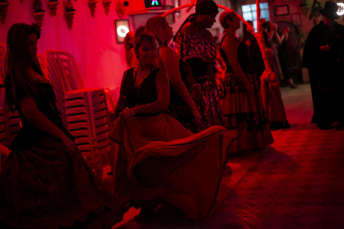 Devotees dance during an Umbanda religious ceremony at the Casa de Caridade Santa Barbara Iansa temple in Rio de Janeiro, Brazil, Saturday, Feb. 6, 2021. The faithful of the Umbanda religion, brought to America by West African slaves, perform spiritual protection rituals as part of pre-Carnival traditions. (AP Photo/Bruna Prado)