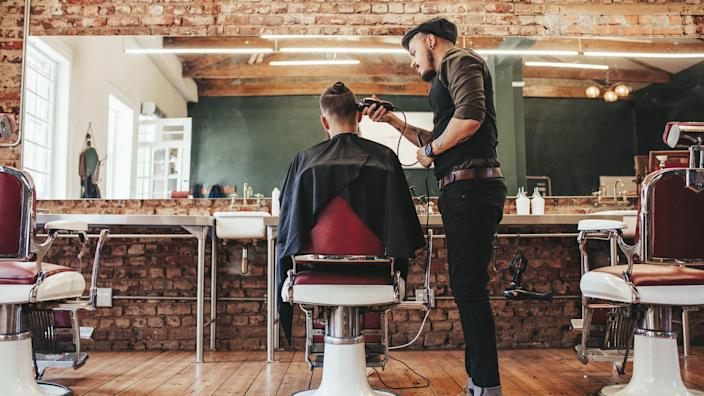 Rear view shot of handsome hairdresser cutting hair of male client.