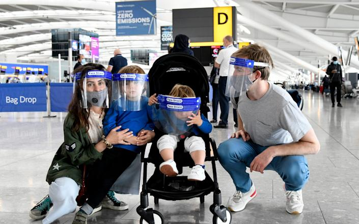 A family wait at Heathrow Airport before departing to Spain for a holiday - David Dyson