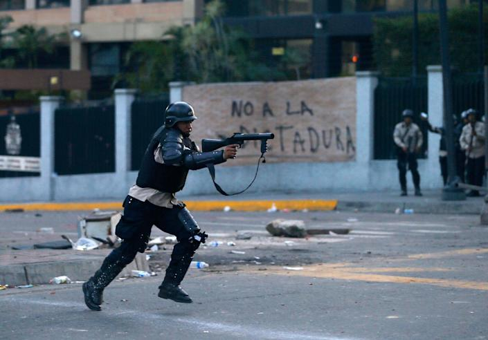 """A policeman fire a tear gas canister to demonstrators during an anti-government protest in Caracas, Venezuela, Saturday, Feb. 22, 2014. After their opposition rally broke up in the late afternoon, in a pattern that has been seen in past demonstrations about 1,000 stragglers erected barricades of trash and other debris and threw rocks and bottles at police and National Guardsmen. The troops responded with volleys of tear gas to prevent the students from reaching a highway and blocking traffic. The writting on the wal in the background reads in Spanish """"No to dictatorship.""""(AP Photo/Fernando Llano)"""
