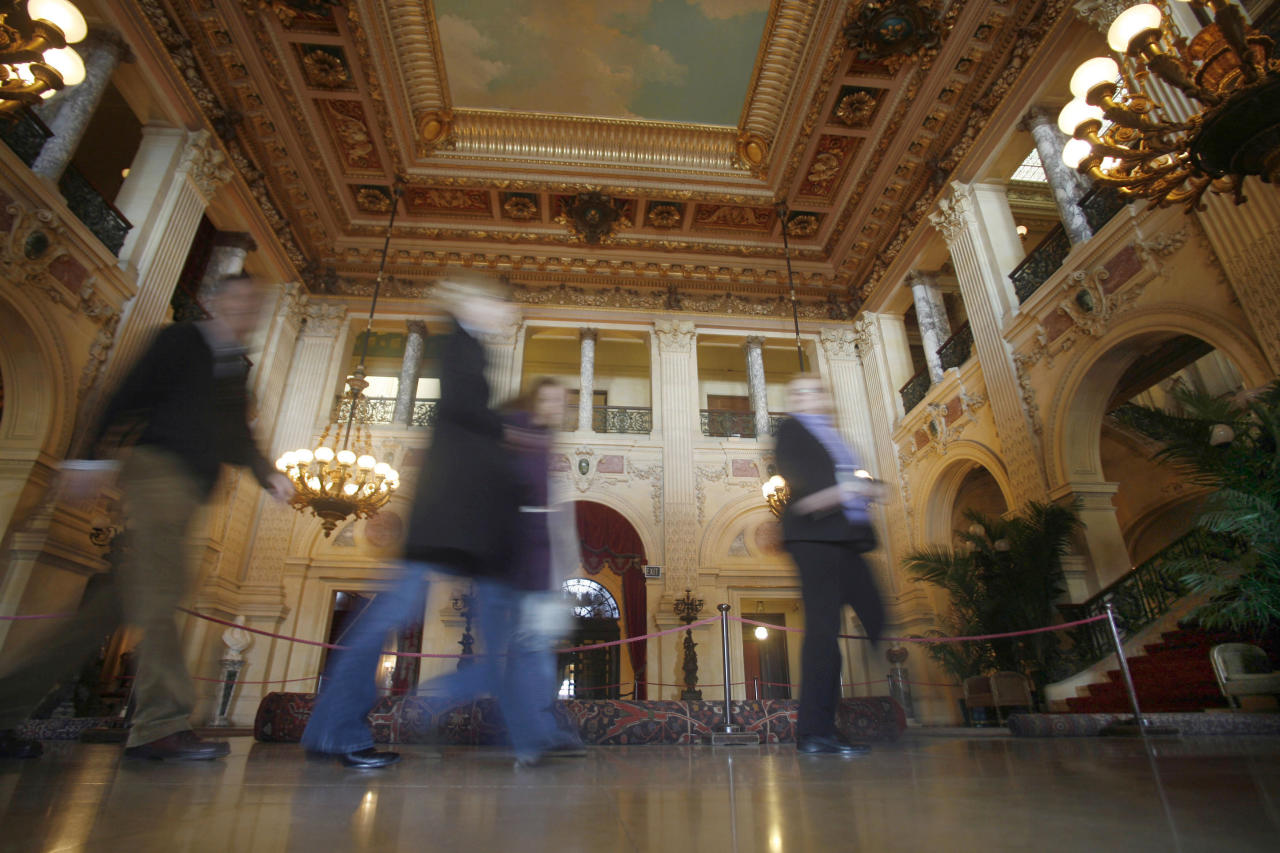 Tourists walk through the Great Hall at The Breakers mansion in Newport, R.I., Tuesday, March 24, 2009. (AP Photo/Stew Milne)