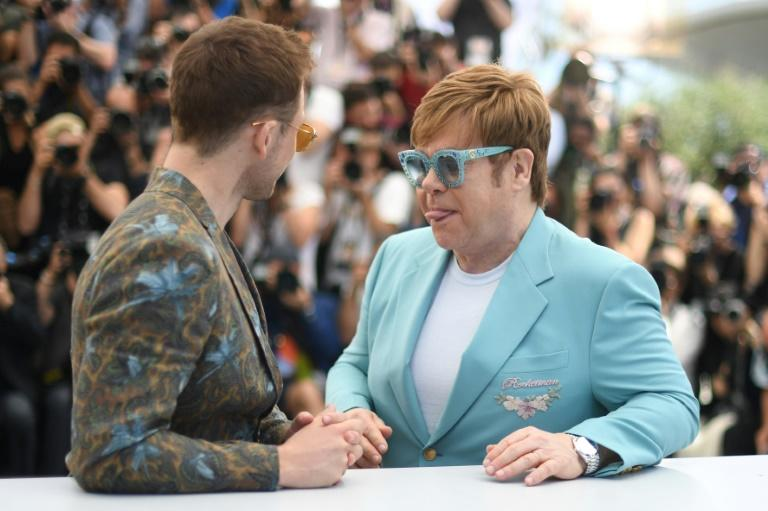 Wearing an eggshell-blue suit and matching diamond-encrusted glasses, Elton John laughed off his limp, sticking his tongue out at Taron Egerton who plays him in the film