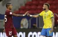 Brazil's Neymar, right, and Venezuela's Richard Celis greet each other with social distance at the end of a Copa America soccer match at the National Stadium in Brasilia, Brazil, Sunday, June 13, 2021. (AP Photo/Eraldo Peres)