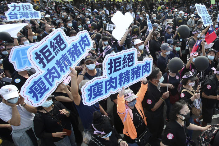 """People hold up signs that read: """"Anti-poisoned pork"""" during a protest in Taipei, Taiwan, Sunday, Nov. 22. 2020. Thousands of people marched in streets on Sunday demanding the reversal of a decision to allow U.S. pork imports into Taiwan, alleging food safety issues. (AP Photo/Chiang Ying-ying)"""