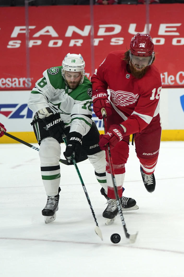 Dallas Stars center Jason Dickinson, left, and Detroit Red Wings defenseman Marc Staal, right, battle for the puck in the first period of an NHL hockey game Thursday, April 22, 2021, in Detroit. (AP Photo/Paul Sancya)
