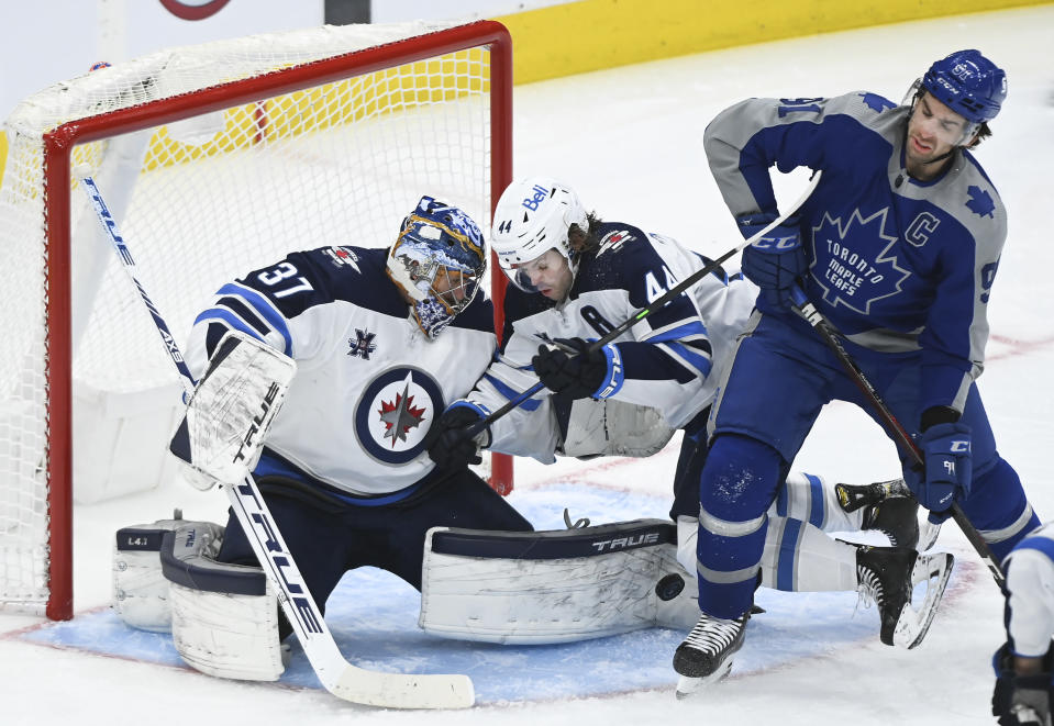 Winnipeg Jets goaltender Connor Hellebuyck (37) makes a pad save next to Toronto Maple Leafs center John Tavares (91) and Jets defenseman Josh Morrissey (44) during the third period of an NHL hockey game Tuesday, March 9, 2021, in Toronto. (Nathan Denette/The Canadian Press via AP)