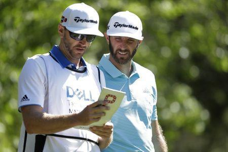 Mar 23, 2017; Austin, TX, USA; Dustin Johnson of the United States, right, goes over the yardage book with his caddie and brother Austin Johnson while playing against Martin Kaymer (not pictured) of Germany during the second round of the World Golf Classic - Dell Match Play golf tournament at Austin Country Club. Erich Schlegel-USA TODAY Sports