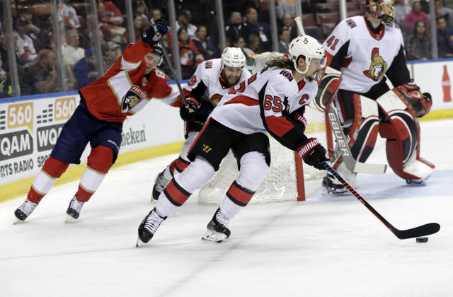 Ottawa Senators' Erik Karlsson (65) skates with the puck as Florida Panthers' Jamie McGinn, left, pursues during the first period of an NHL hockey game, Monday, March 12, 2018, in Sunrise, Fla. (AP Photo/Lynne Sladky)