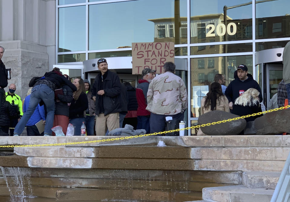 Roughly two dozen people gather to protest mask rules and other measures taken to slow the coronavirus pandemic and to show support for fellow protester and anti-government activist Ammon Bundy outside the Ada County Courthouse in Boise, Idaho, Monday, March 15, 2021. Bundy was scheduled to stand trial on charges that he trespassed and obstructed officers at the Idaho Statehouse during a special legislative session last fall, but Magistrate Judge David Manweiler issued a warrant for Bundy's arrest after Bundy failed to appear in the courtroom. Bundy was arrested late Monday morning on a misdemeanor charge of failing to appear in court. (AP Photo/Rebecca Boone)