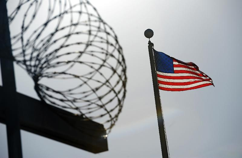 """A US flag flies above a razorwire-topped fence at the """"Camp Six"""" detention facility December 10, 2008 at the US Naval Station in Guantanamo Bay, Cuba"""
