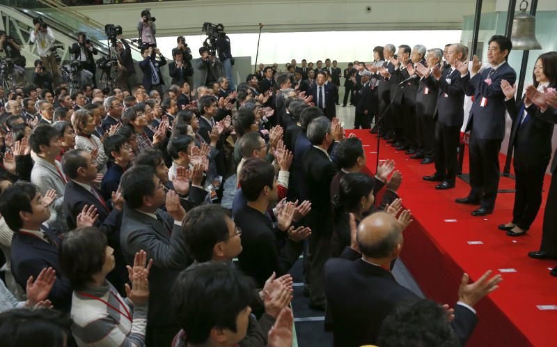 """Japanese Prime Minister Shinzo Abe, second from right, and participants conduct a traditional handclap at the end of a ceremony to wrap up the year's trading on the Tokyo Stock Exchange in Tokyo Monday, Dec. 30, 2013. """"Thanks to our efforts, the economy went from minus to positive,"""" Abe said. With winter bonuses up by several hundred dollars on average, he said, """"You have to use that money, keep it moving."""" Asian shares advanced Monday in light but upbeat pre-holiday trading, as Japan's Nikkei 225 index ended 2013 at its highest level in over six years. (AP Photo/Shizuo Kambayashi)"""