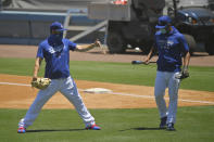 Members of the Los Angeles Dodgers warm up during the restart of spring baseball training, Friday, July 3, 2020, in Los Angeles. (AP Photo/Mark J. Terrill)