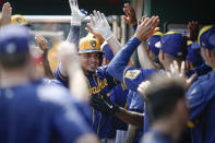 Milwaukee Brewers' Willy Adames celebrates with teammates after scoring during the ninth inning of a baseball game against the Cincinnati Reds in Cincinnati, Sunday, July 18, 2021. (AP Photo/Bryan Woolston)