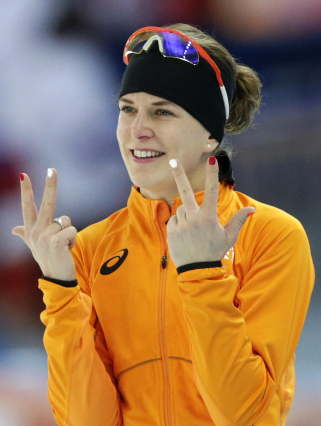 Ireen Wust of the Netherlands flashes three fingers in each hand, indicating her third olympic gold medal, after winning gold in the women's 3,000-meter speedskating race at the Adler Arena Skating Center during the 2014 Winter Olympics, Sunday, Feb. 9, 2014, in Sochi, Russia. (AP Photo/Matt Dunham)