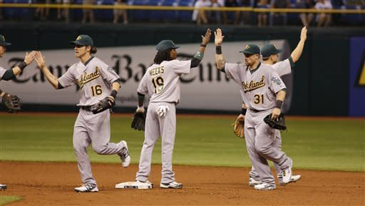 Oakland Athletics Jonny Gomes (31) celebrates with teammates after beating the Tampa Bay Rays in 12 innings of a baseball game, Saturday, May 5, 2012, in St. Petersburg, Fla. (AP Photo/Scott Iskowitz)