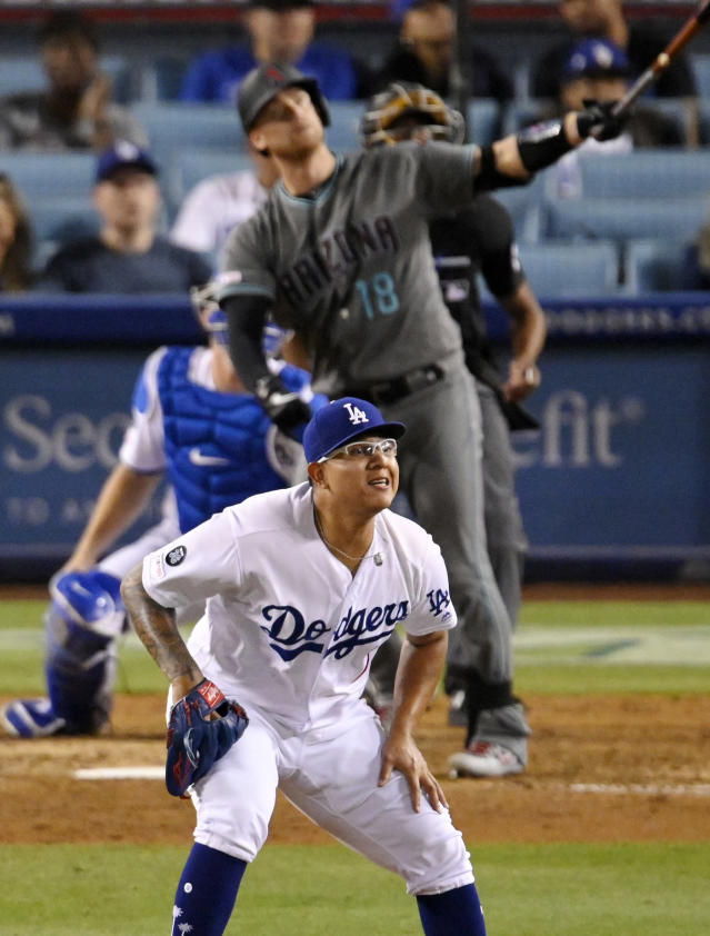 Arizona Diamondbacks' Carson Kelly, top, hits a solo home run as Los Angeles Dodgers relief pitcher Julio Urias reacts during the 11th inning of a baseball game Friday, Aug. 9, 2019, in Los Angeles. (AP Photo/Mark J. Terrill)