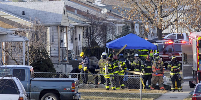 South Bend police and fire officials examine a home where a a plane crash occurred near the South Bend Regional Airport Sunday, March 17, 2013 in South Bend, Ind. The private jet apparently experiencing mechanical trouble crashed in the northern Indiana neighborhood, resulting in injuries and striking three homes, authorities and witnesses said. (AP Photo/Joe Raymond)