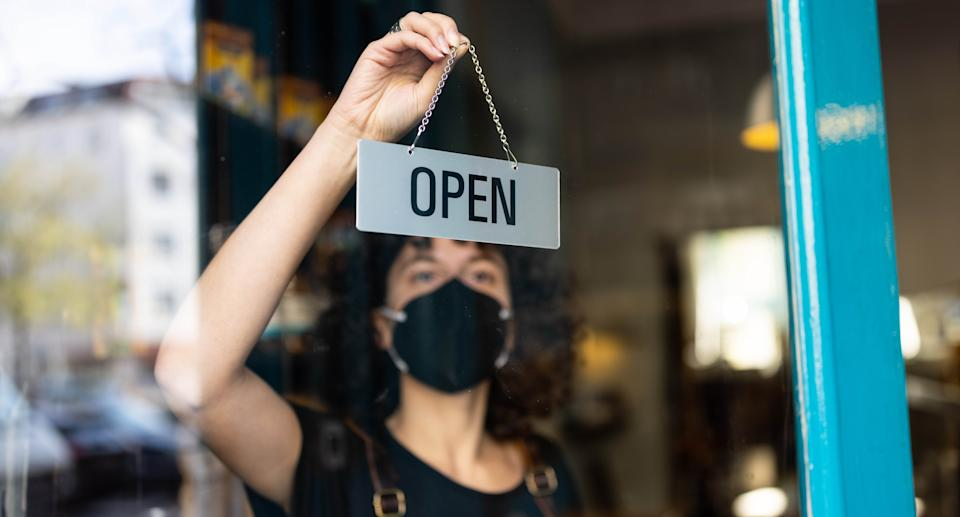 Young non-binary person hanging an open sign from the door of a small bakery. Source: Getty Images