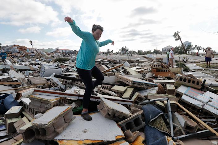 Mishelle McPherson climbs over the rubble of her friend's home. McPherson is searching for her friend because she knows she stayed in the home during Hurricane Michael.