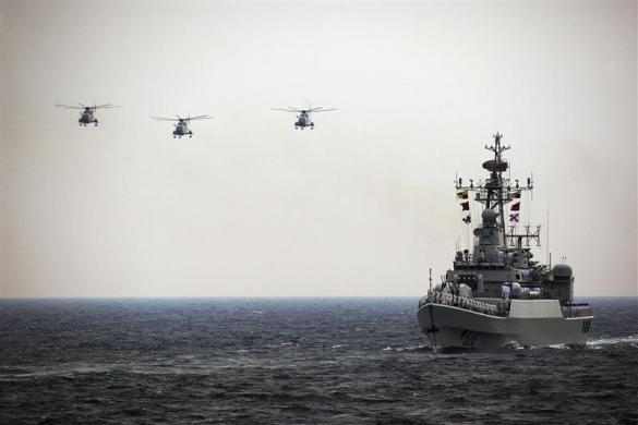 """Helicopters accompany the Chinese Jiangwei II naval frigate """"Mianyang"""" during an international fleet review to celebrate the 60th anniversary of the founding of the People's Liberation Army Navy in Qingdao, Shandong province April 23, 2009."""