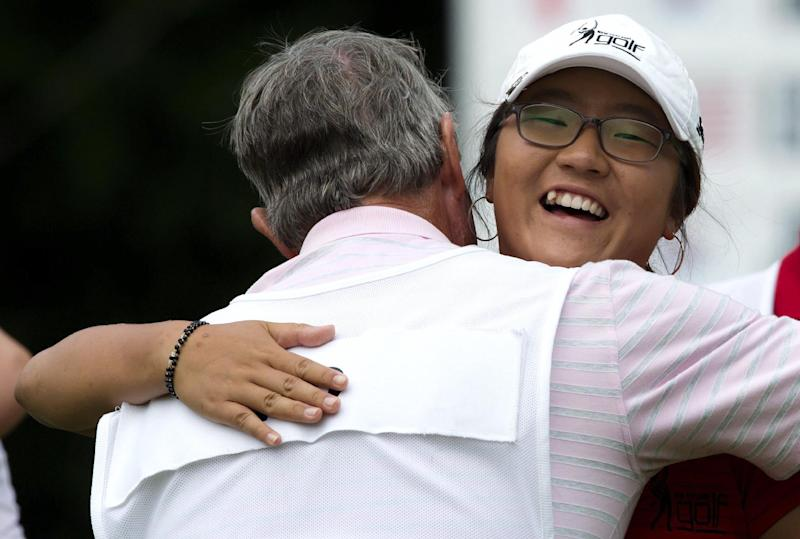Lydia Ko, of New Zealand, hugs her caddie Brian Alexander after winning the LPGA Tour's Canadian Women's Open golf tournament, Sunday, Aug. 26, 2012, at the Vancouver Golf Club in Coquitlam, British Columbia. (AP Photo/The Canadian Press, Darryl Dyck)