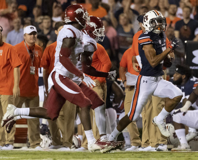 Auburn wide receiver Anthony Schwartz (5) breaks loose for a long pass as Arkansas defensive backs Kamren Curl (2) (near) and Santos Ramirez (9) follow during the first half of an NCAA college football game, Saturday, Sept. 22, 2018, in Auburn, Ala. (AP Photo/Vasha Hunt)