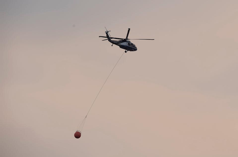 A helicopter carries water to fight the Cameron Peak Fire in Fort Collins, Colo. on Tuesday, Oct. 20, 2020.