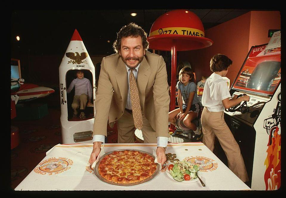 "<p>Bushnell built the concept of his restaurant on the idea of a carnival. He wanted atmosphere that would allow families to gather, while introducing children to video games. He settled on the name Chuck E. Cheese for his mouse mascot, because it <a href=""http://showbizpizza.com/info/history/history.html"" rel=""nofollow noopener"" target=""_blank"" data-ylk=""slk:forced people to smile"" class=""link rapid-noclick-resp"">forced people to smile </a>when they said it.</p>"